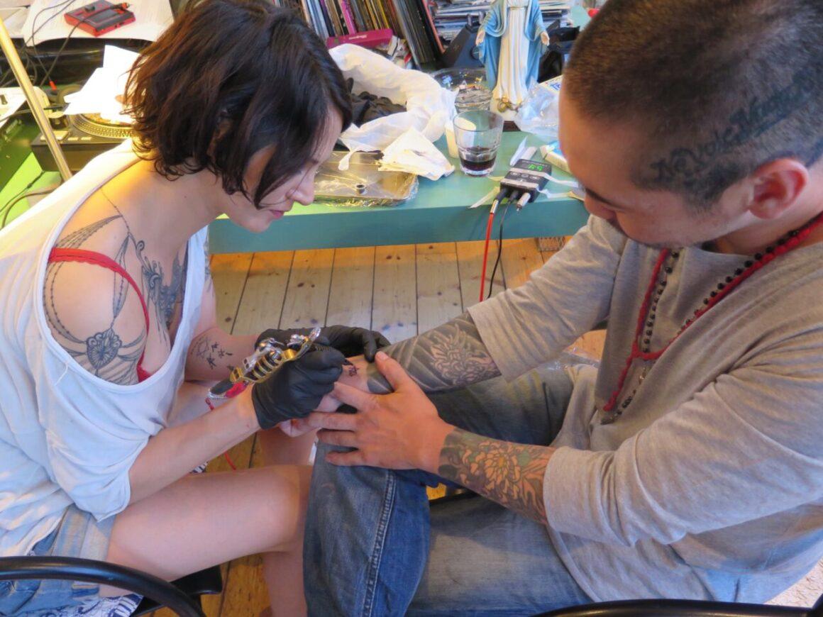 Asia makes tattoo to Akilla, courtesy of Akilla
